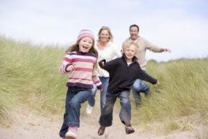 En familie som løper på stranden, Foto: Colourbox